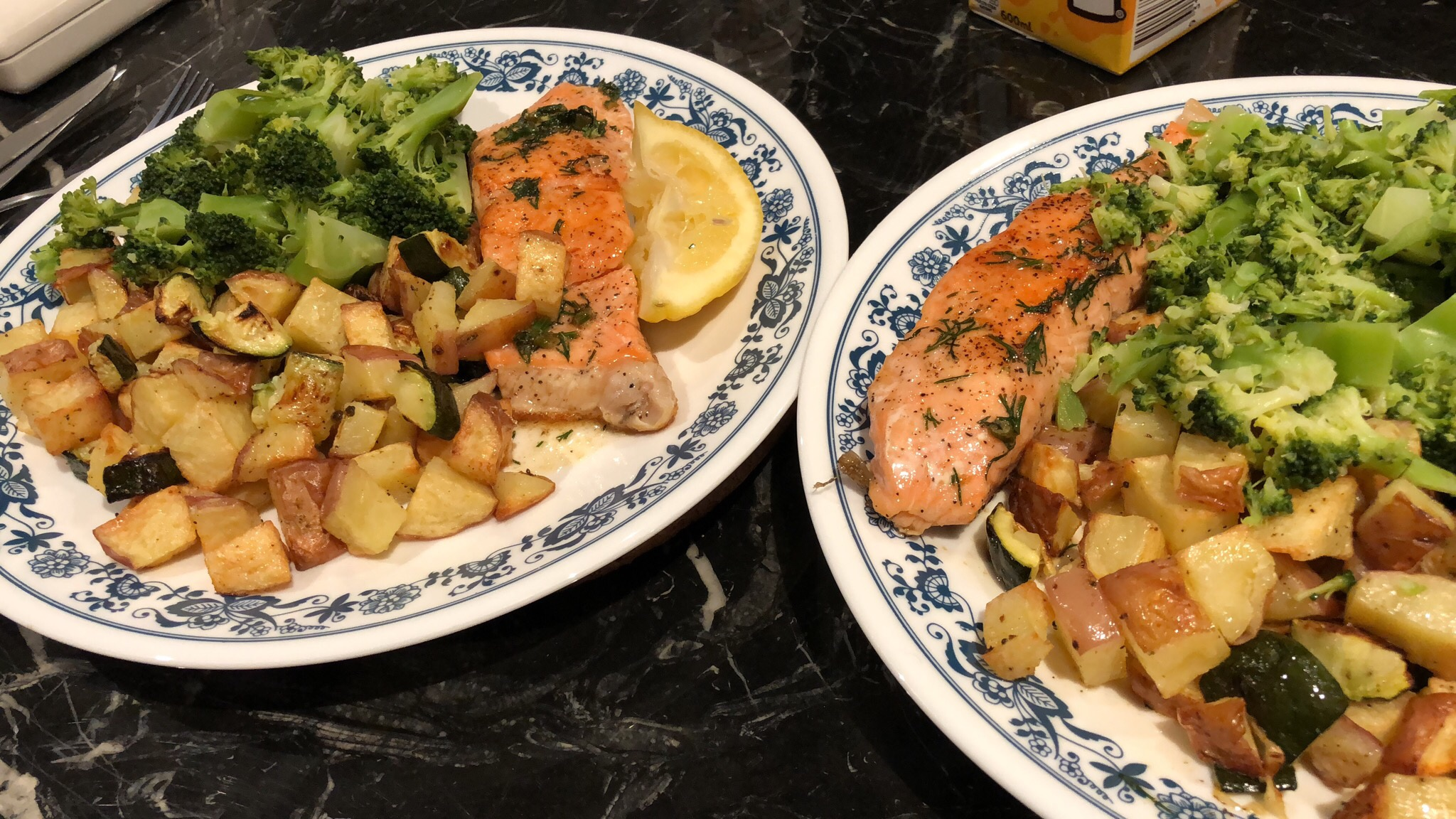 Two plates with seared salmon, chopped up potatoes and broccoli drizzled with butter dill sauce.